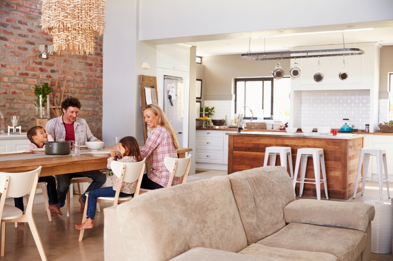 A young family in a tidy home sitting down together for a meal