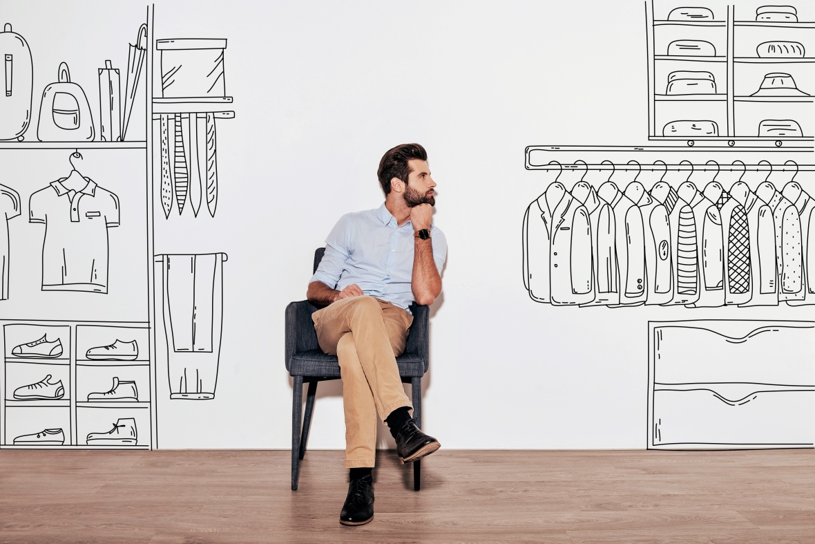Young handsome man keeping hand on chin and looking away while sitting in the chair against illustration of an organized closet in the background